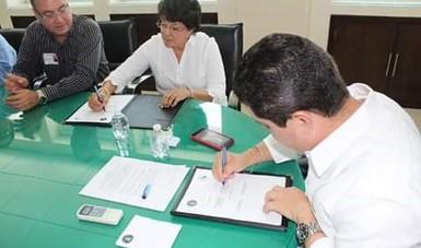 Dos personas firmando un convenio de colaboración