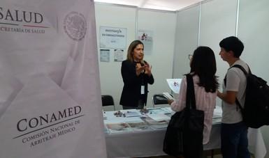 Una mujer brindado información sobre Servicio Social  a dos estudiantes en el stand de investigación en farmacoterapia