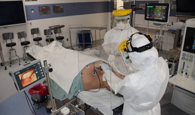 Dos mñedicos anvales en traje bacteriologico atienden a un paciente de Covid recostado enuna camilla