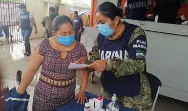 Dos personas de pie, una vestida de civil, la segunda con uniforme pixelado de la Marina, al frente hay una mesa con medicamentos