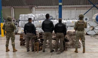 cinco persona dando la espalda y frente a ellos paquete apilados con posible droga