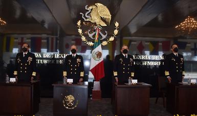 Cuatro personas con uniforme negro de gala de la secretaría de marina, al fondo se observa la bandera nacional y el escudo de armas de la Secretaría de Marina-Armada de México