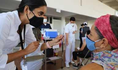 Enfermera mostrando vacuna a maestra