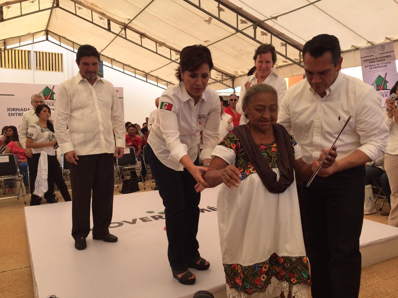 """La titular de SEDATU, Rosario Robles Berlanga, ayuda a Benita, una persona con discapacidad, y quien es una beneficiaria de los programas de """"Vivienda para Prosperar"""", ya que se le entregará una vivienda modificada con señalizaciones especiales."""