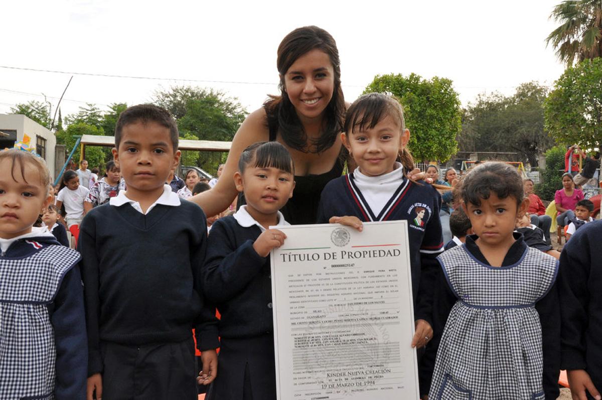 Maestra con niños de kinder recibiendo Título de Propiedad.