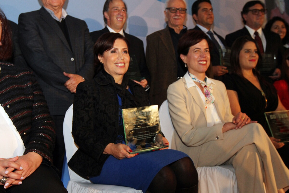 Rosario Robles, titular de SEDATU, está sentada sonriendo y sosteniendo entre sus manos su reconocimiento.