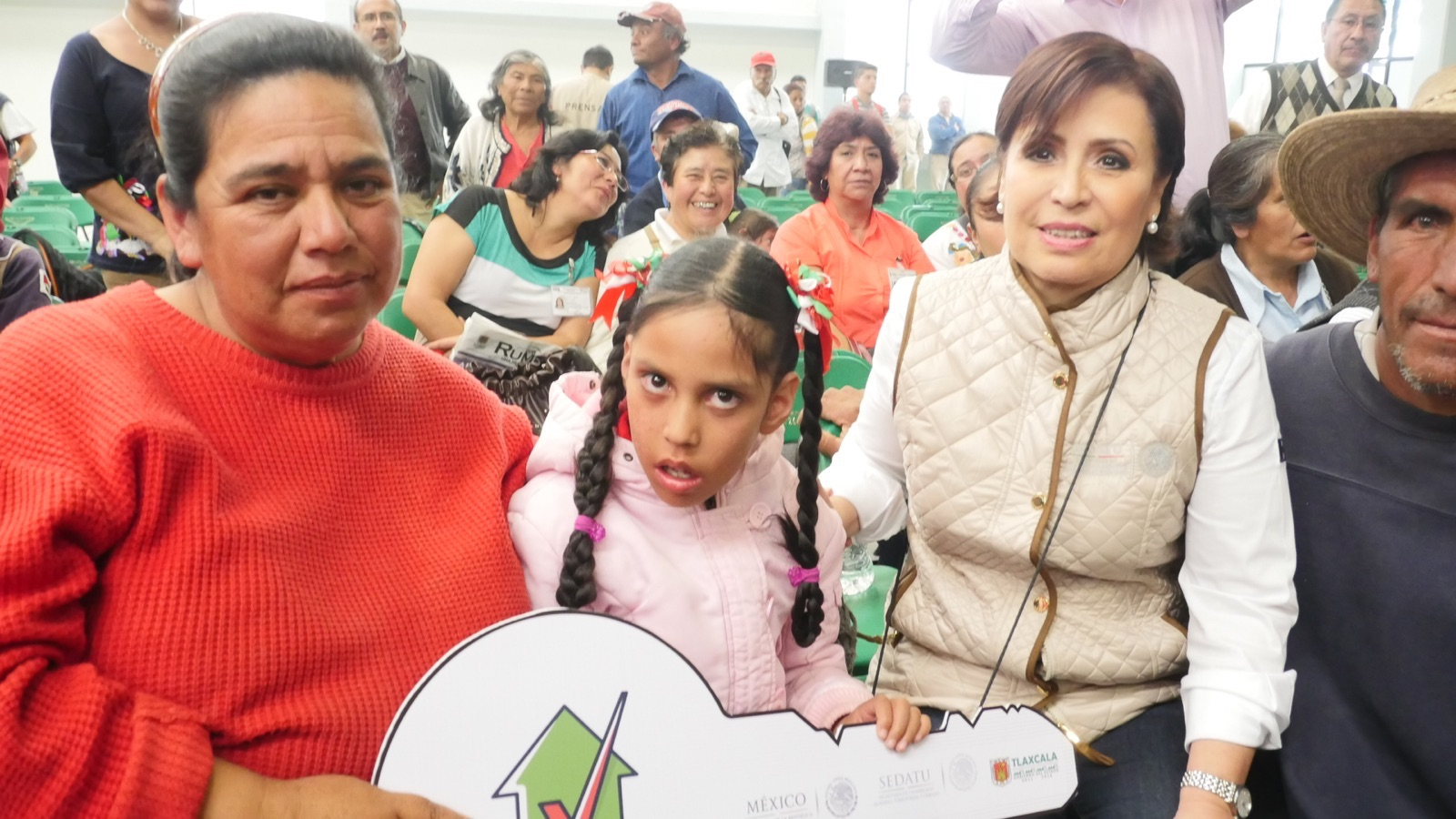 La titular de SEDATU, Rosario Robles, entregando simbólicamente a niñas, niños y mujeres con discapacidad las llaves de su nueva vivienda acondicionada especialmente para cubrir sus necesidades especiales.