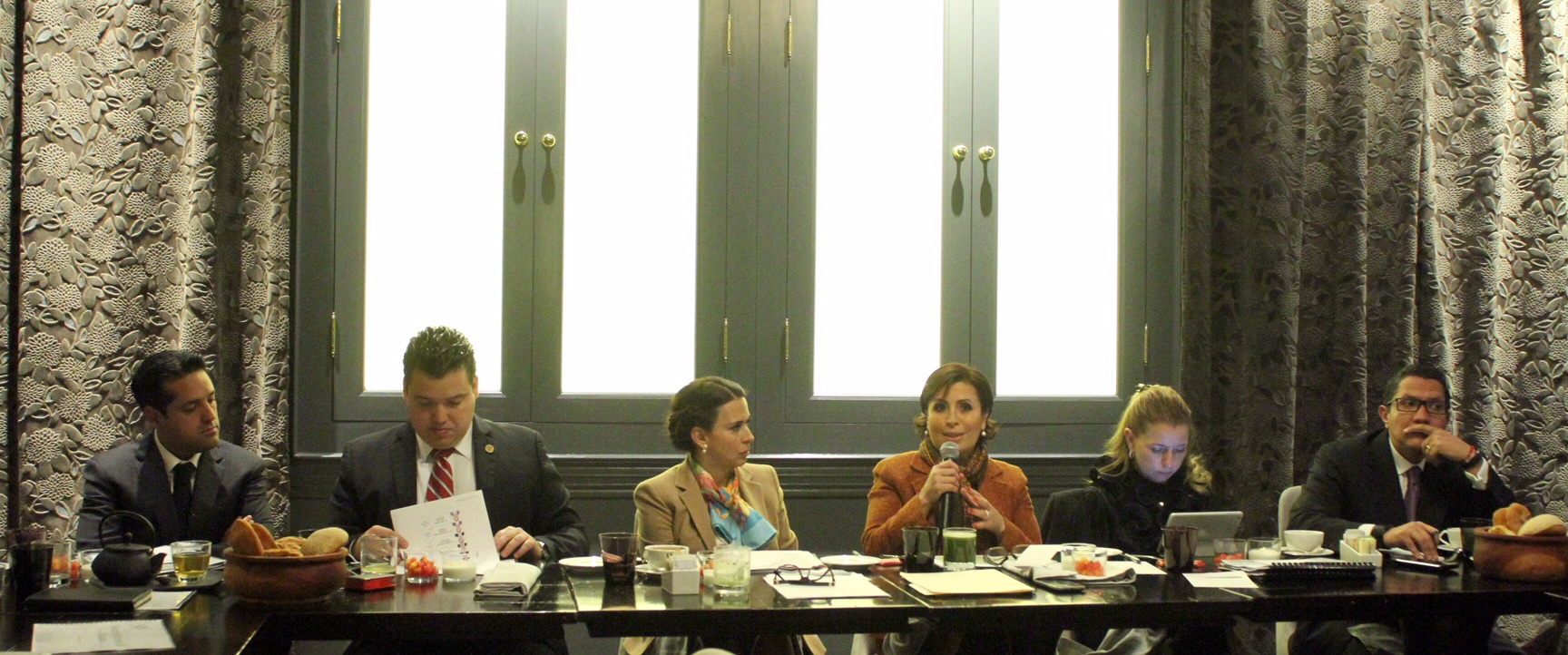 La titular de la SEDATU, Rosario Robles, sentada alrededor de una amplia mesa con integrantes de la Comisión de Vivienda de la Cámara de Diputados, para discutir temas de la agenda de la Secretaría.
