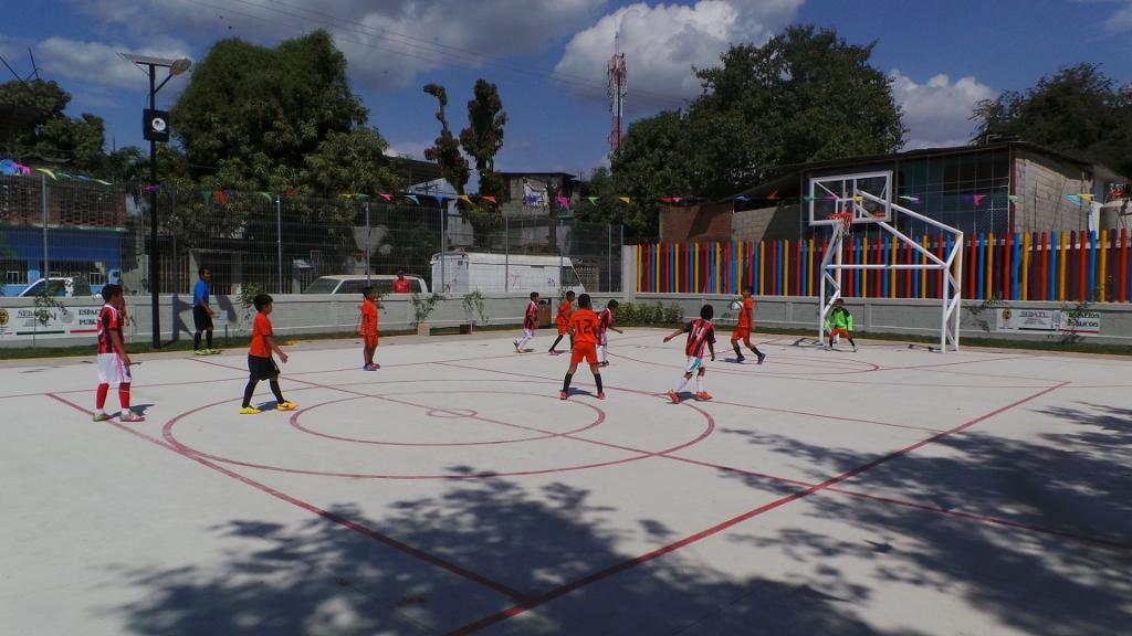 En la gráfica, un grupo de niños juega basquetbol. Cada vez más, en el estado de Guerrero, miles de personas se siguen beneficiando gracias al programa de Rescate de Espacios Públicos.