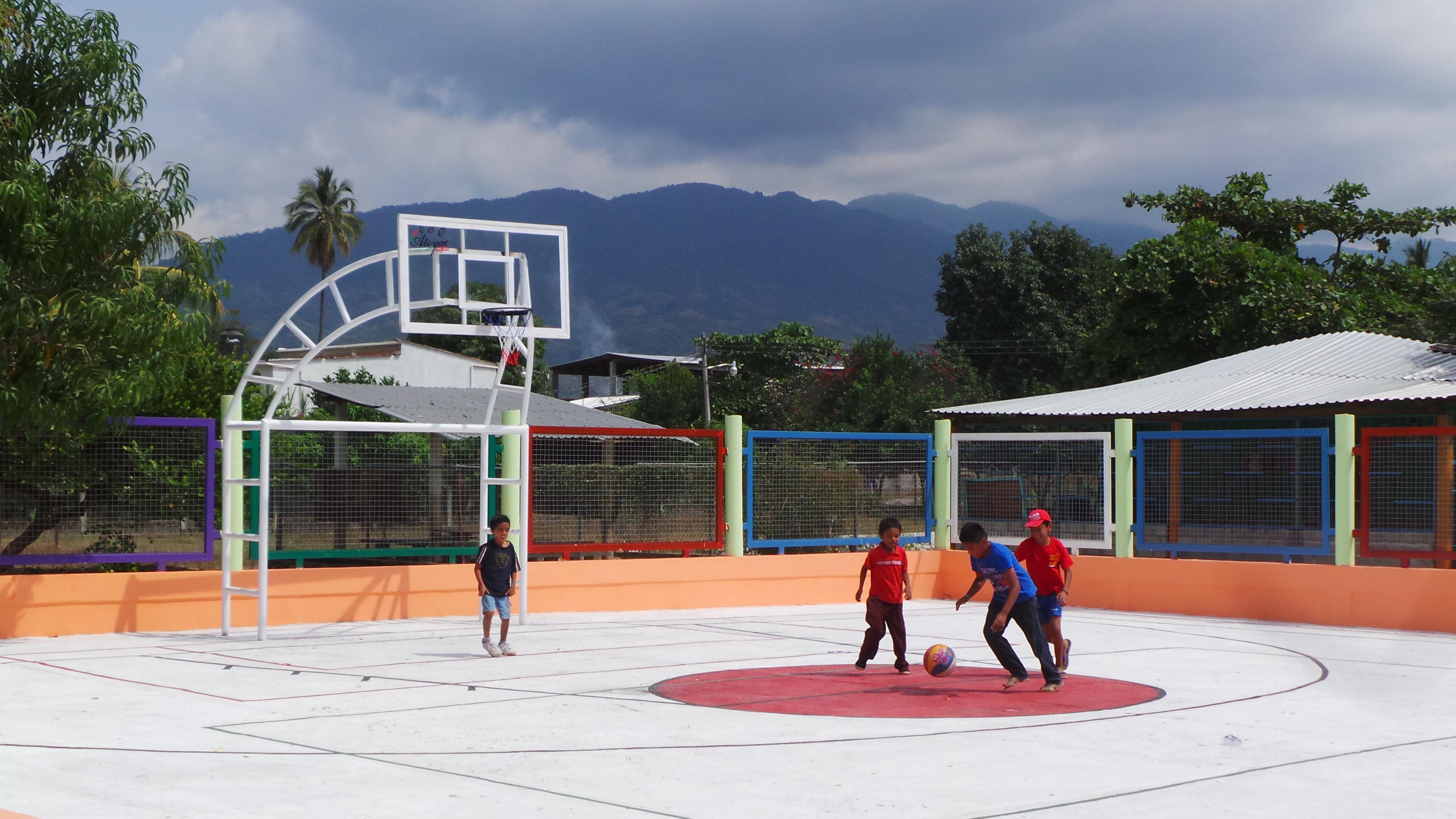 """En la gráfica, un grupo de niños juega basquetbol en el recién inaugurado -por la SEDATU en la Costa Grande- parque recreativo """"Las Palmeras"""", que beneficia a unas 300 personas."""